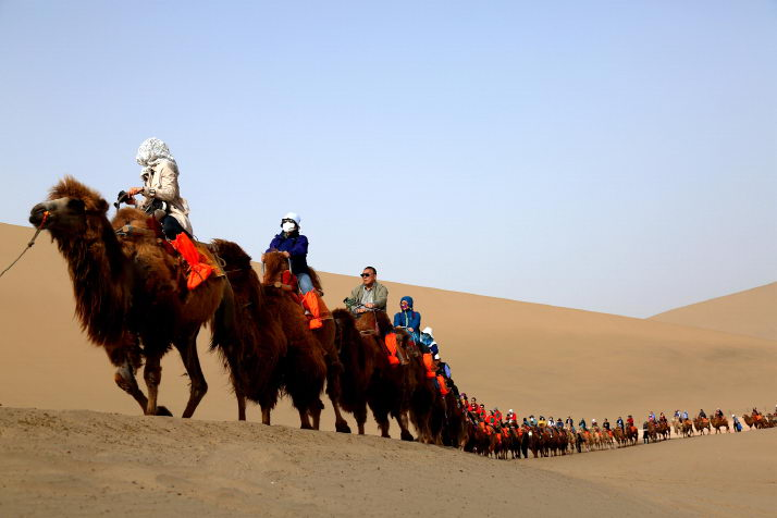 Travelers are touring the Mingsha Mountain and the Yueya Lake near Dunhuang City of Gansu Province on April 30 (XINHUA)