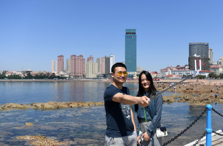 Visitors take a selfie at a scenic spot in Qingdao, east China's Shandong Province, on May 31 (XINHUA)