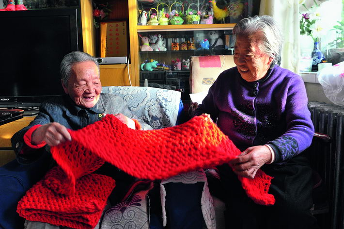 November 19, 2013: 100-year-old Su Fengzhu (left) and her 83-year-old friend Zhang Yunying inspect a scarf they have just finished knitting, in Yinchuan City. VCG