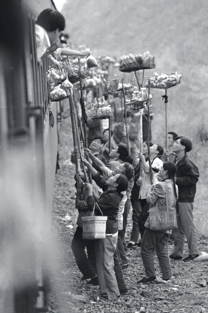 "October 1996: At a small station called Qiangzilu on the railway route from Beijing to Qinhuangdao City, villagers sell local specialties to passengers. The train stopped for only five minutes and the station lacked a platform, so villagers invented a new method to sell their goods.  by Zhou Chaorong   In the mid-1990s, China was shifting from a planned economy to a market economy. Commerce prospered across the country, as evidenced by the axiom ""900 million out of a billion Chinese people are businesspeople."""
