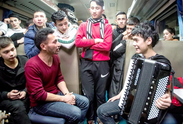 In a still from the second episode of the documentary, young Uygur poet Niyazi Ali (second left) talks to other passengers on a train.