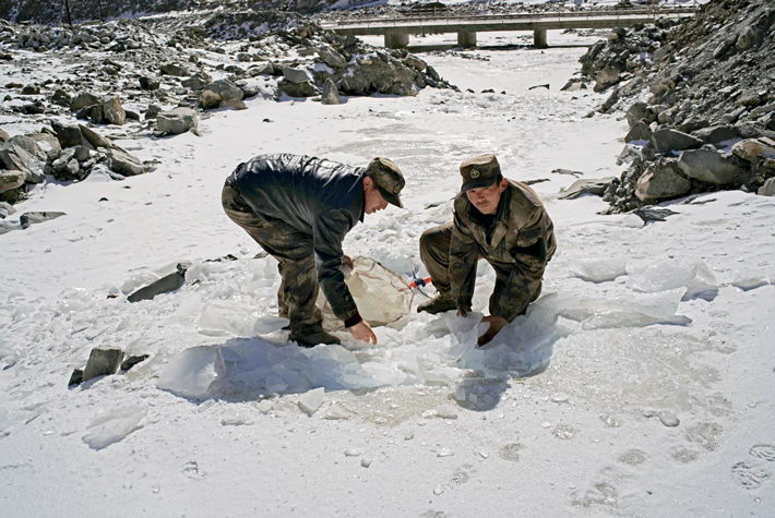In Tugurmiti Township, border protection workers brave the cold to chisel blocks of ice to melt for water for cooking and washing in winter.