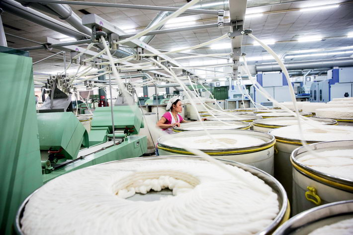 A spinning workshop at the textile factory of Huaxi Village in Jiangyin.  by Qin Bin