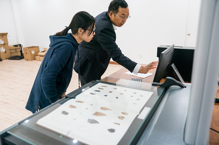 Liu Yongge (right) instructs his student to scan oracle bone inscriptions and put them into the big data platform. At present, the platform has collected 246 oracle bone script catalogs and published 46 of them.  by Xu Xun